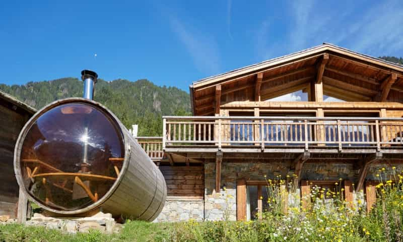 a chalet in the mountain with an outdoor sauna
