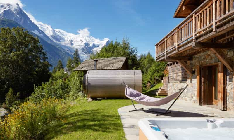 an outdoor sauna and hammock in the mountain