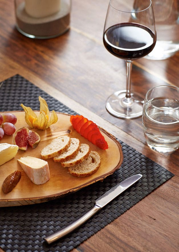 image of a cheeseboard and a glass of wine