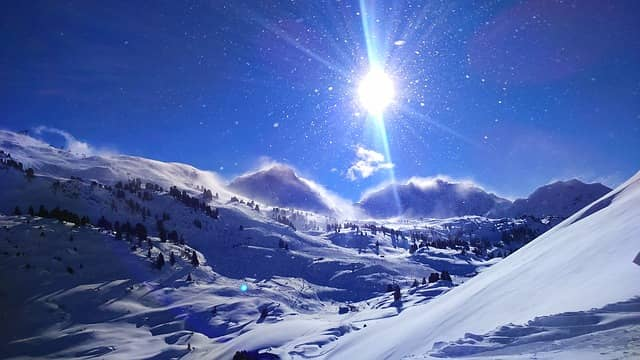 image of sun blazing down on snow resort