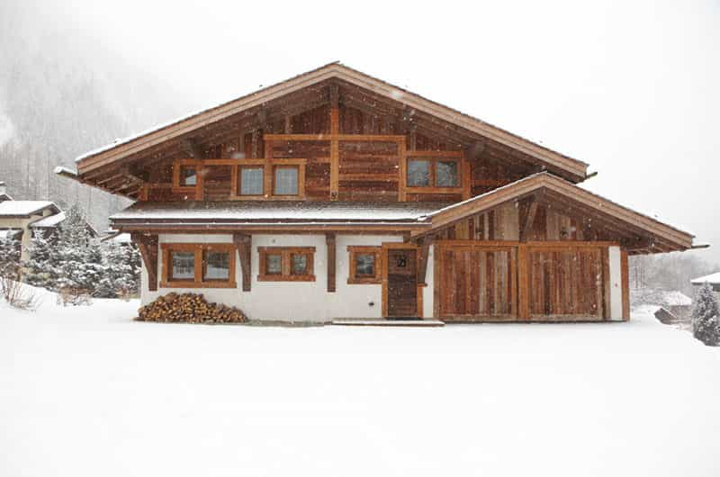 an image of a chalet under strong snow