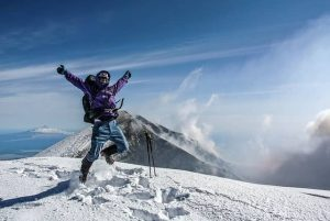 man celebrating on top of a snowy mountain